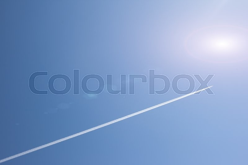 Stock image of 'trace of the plane in the blue sky flying to the sun'