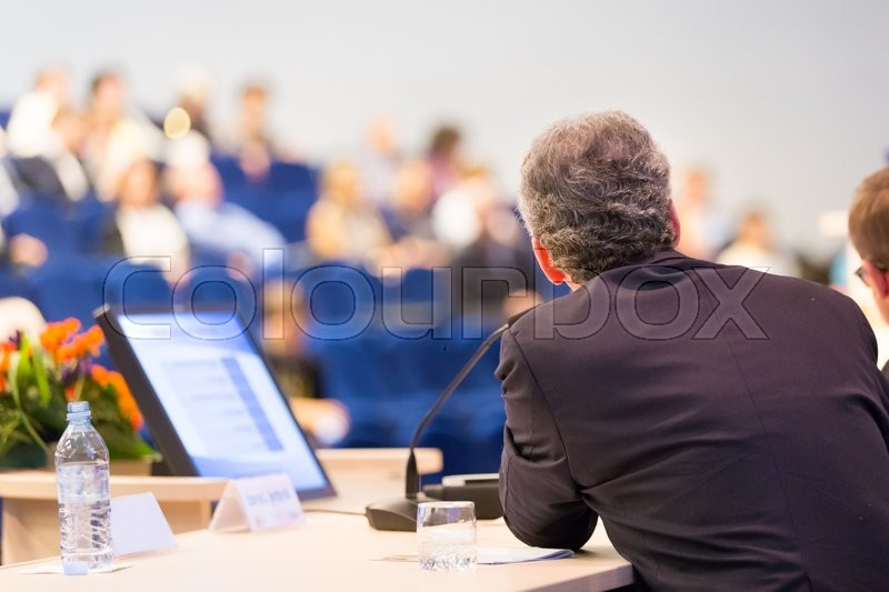 Stock image of 'Speaker at Business Conference with Public Presentations. Audience at the conference hall. Entrepreneurship club. Rear view. Horisontal composition. Background blur.'