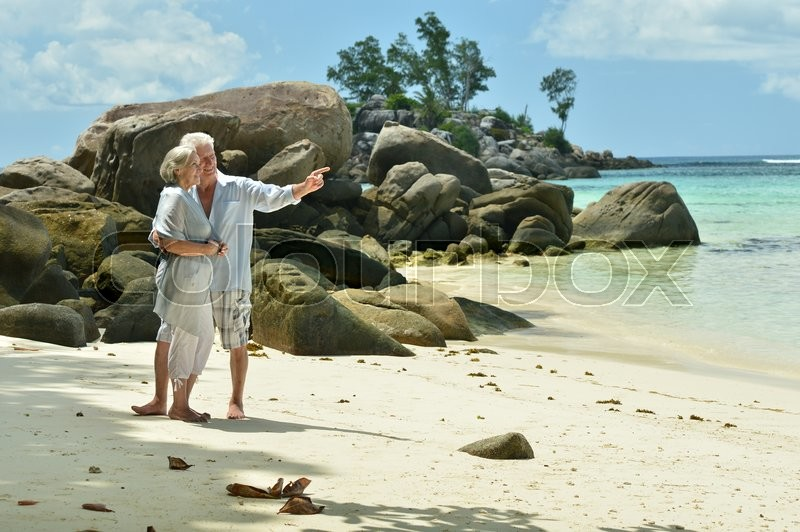 Stock image of 'Happy elderly couple rest at tropical beach,man pointing by his hand'