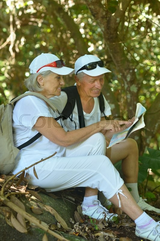 Stock image of 'Beautiful happy elderly couple rest at tropical resort with backpacks and map'