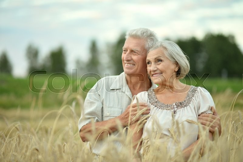 Stock image of 'Beautiful happy senior couple in summer field'