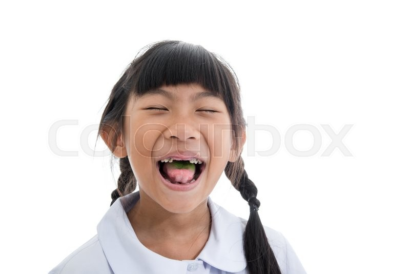Stock image of 'Cute Asian girl in uniform showing her broken teeth on white background.'