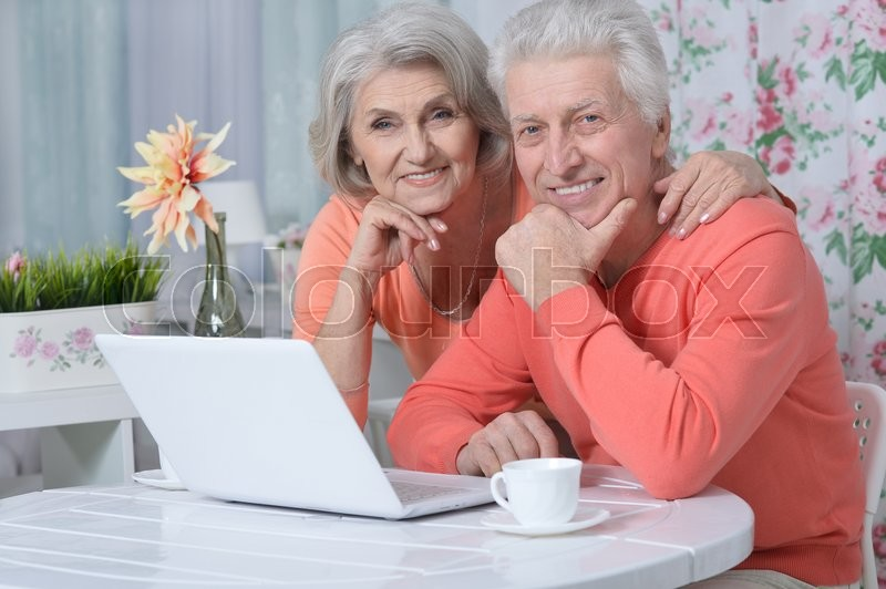 Stock image of 'happy senior couple with laptop  at home'