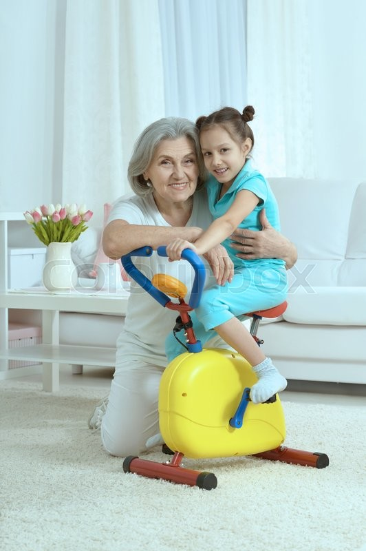 Stock image of 'senior woman and  little granddaughter doing exercise home'