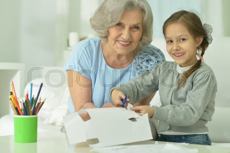 Stock image of 'Portrait of a happy grandmother with granddaughter cutting together'