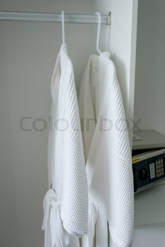 Stock image of 'Hanging white robes in room'