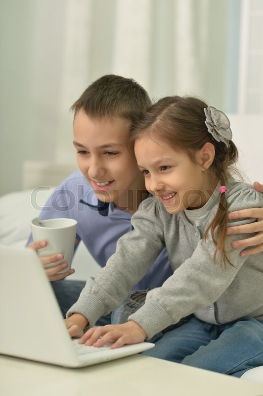 Stock image of 'Portrait of a happy children with laptop at home'