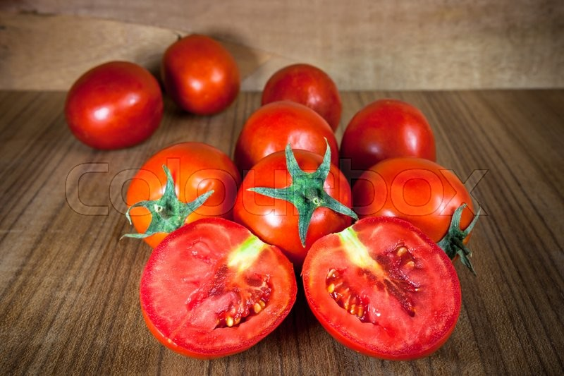 Stock image of 'Close-up fresh ripe tomatoes on wood background .'