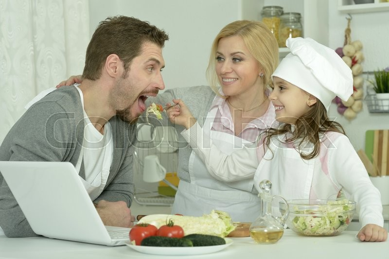 Stock image of 'portrait of happy family cooking  in kitchen with laptop'