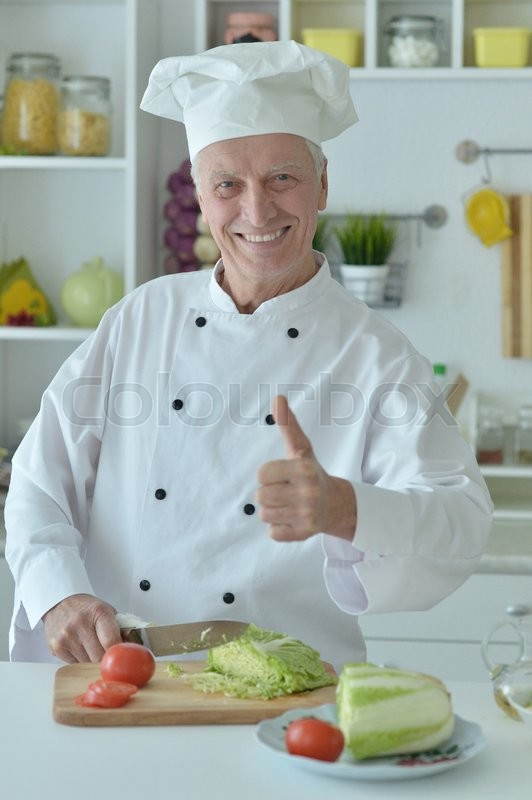 Stock image of 'Portrait of a elderly male chef cooking salad'