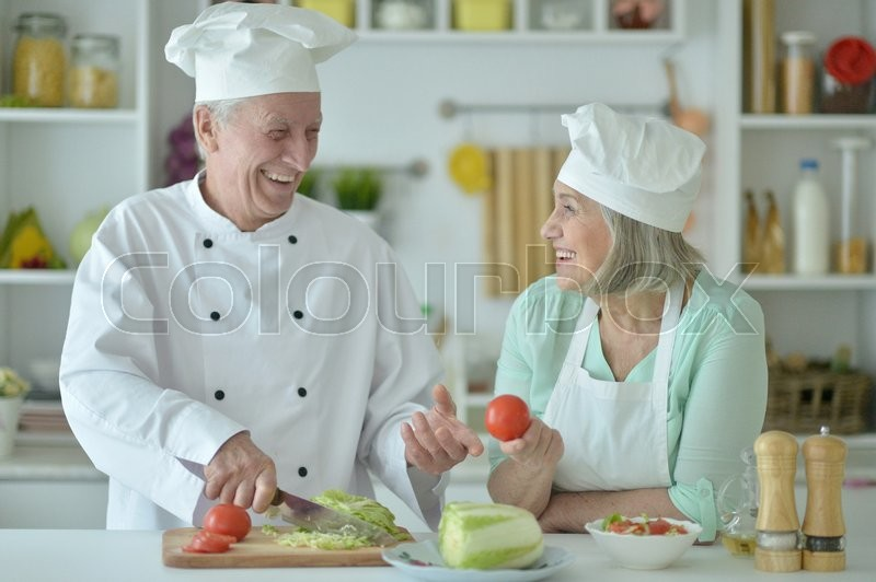 Stock image of 'Portrait of a senior couple at kitchen cooking'