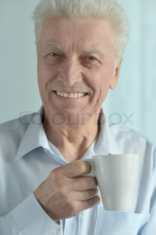 Stock image of 'Portrait of a happy senior man with cup'