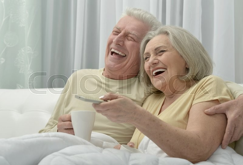 Stock image of 'Portrait of a happy senior couple resting in bed'