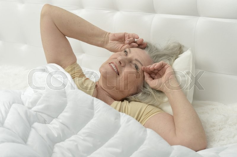 Stock image of 'Portrait of a senior woman in bed reading'