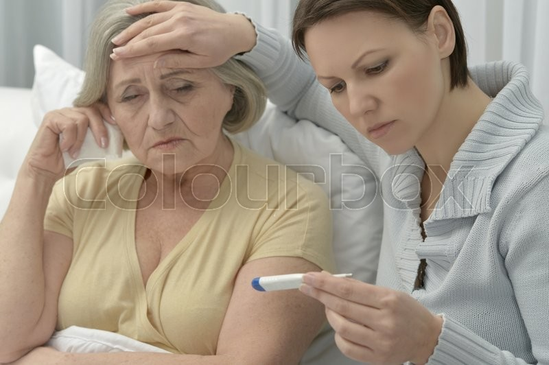 Stock image of 'ill Senior woman with caring daughter with thermometer'