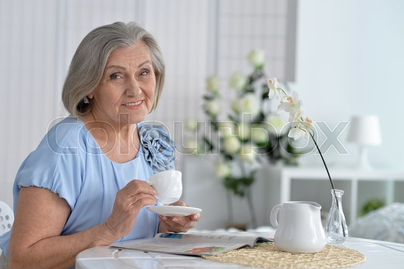 Stock image of 'Portrait of mature woman with coffee at home'