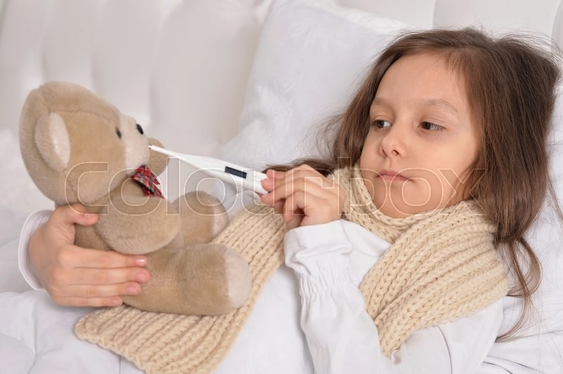 Stock image of 'Sad sick little girl lying in the bed with teddy bear toy'