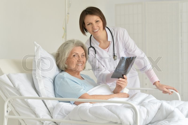Stock image of 'Senior woman portrait in hospital with caring doctor'