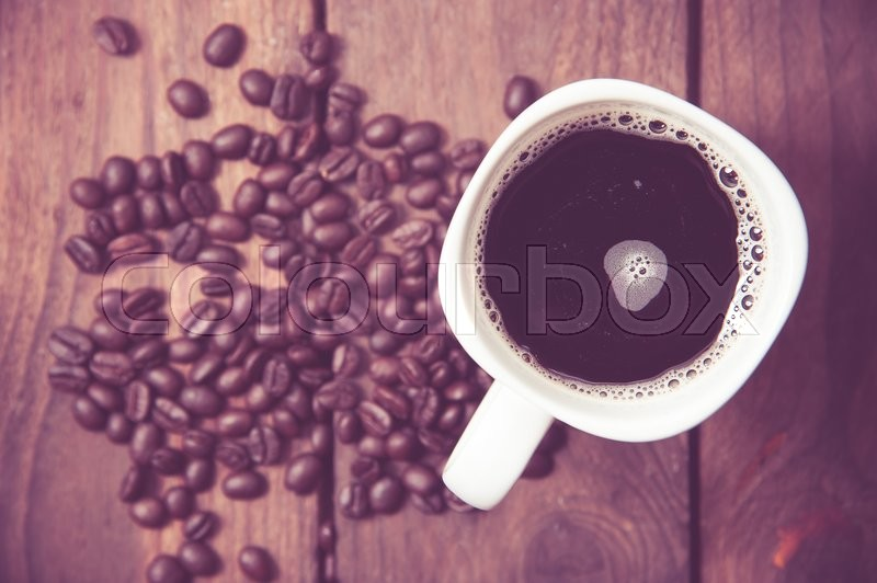 Stock image of 'Top view on cup of coffee over grunge wooden bacgkround ,vintage color toned image'