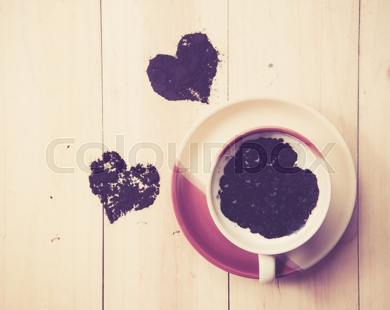 Stock image of 'Cup of coffee with cacao heart on wood ,vintage color toned image'