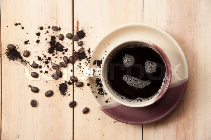 Stock image of 'Espresso Cup with smiley face on wooden table, overhead view ,vintage color toned image'