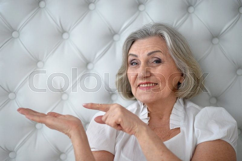 Stock image of 'happy Senior woman portrait pointing at copy space'