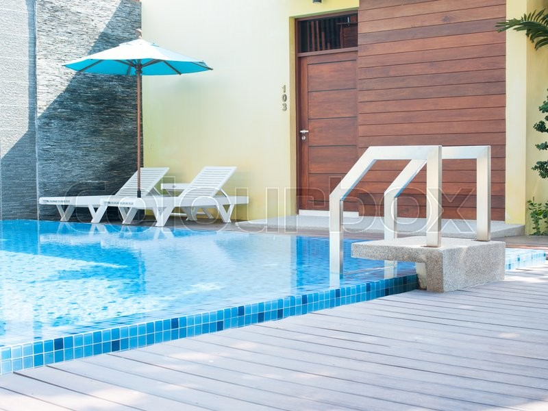 Stock image of 'Clean swimming pool and empty resting chair'