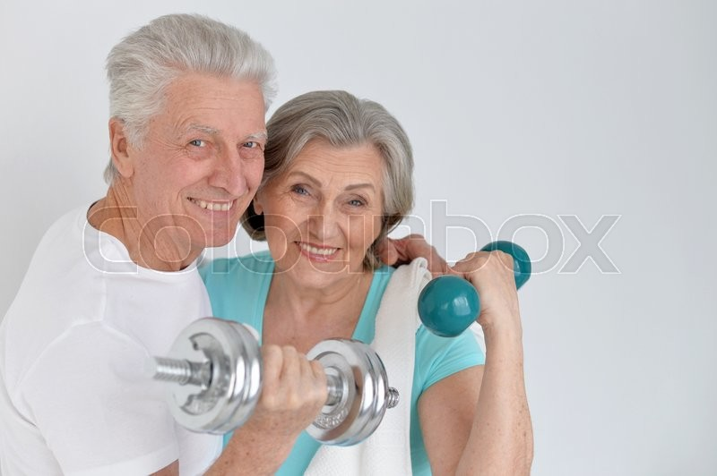 Stock image of 'Happy sporty senior couple exercising with dumbbells'