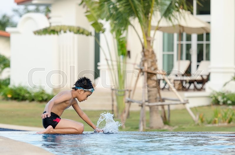 Stock image of 'Activities on the pool, child sitting at swimming pool in summertime'