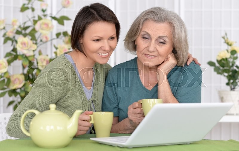 Stock image of 'senior mother and adult daughter working with laptop together'
