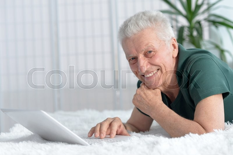 Stock image of 'Portrait of a happy senior man using laptop'