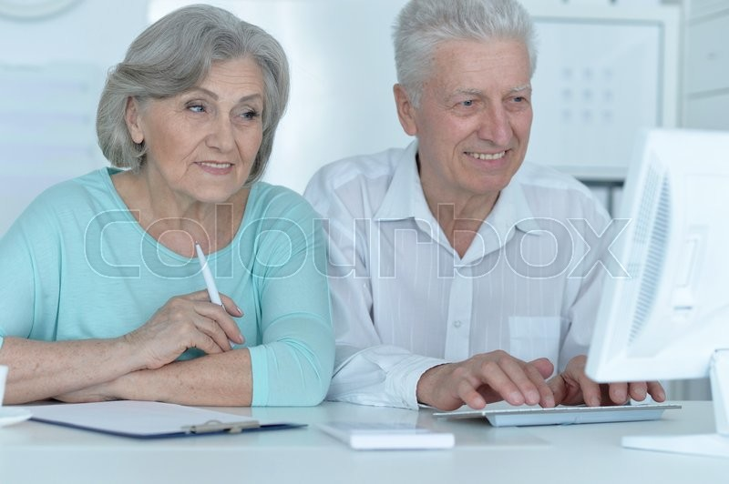 Stock image of 'Portrait of a senior couple working with computer'