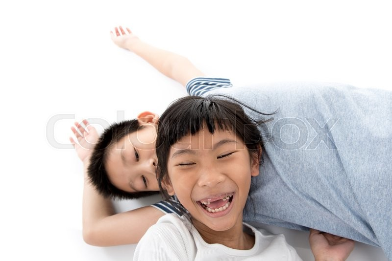 Stock image of 'Close up Young sister laying on her brother with white background.'