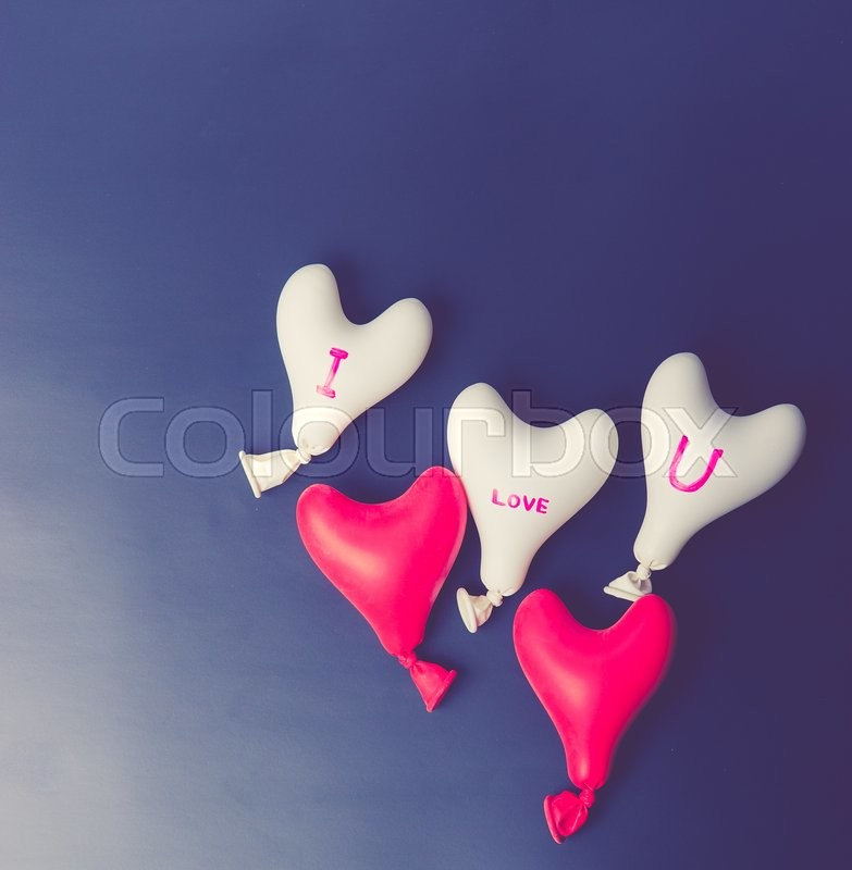 Stock image of 'Valentine day concept.red and white heart balloon on a black slate,vintage color toned image'