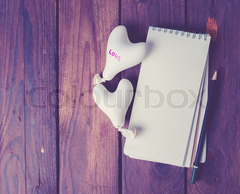Stock image of 'Valentine day concept.heart balloon with notebook on wood,vintage color toned image'
