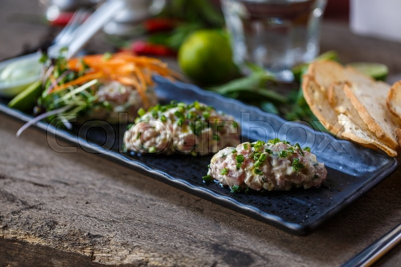 Stock image of 'Fish tartare with herbs and carrot in the restaurant'