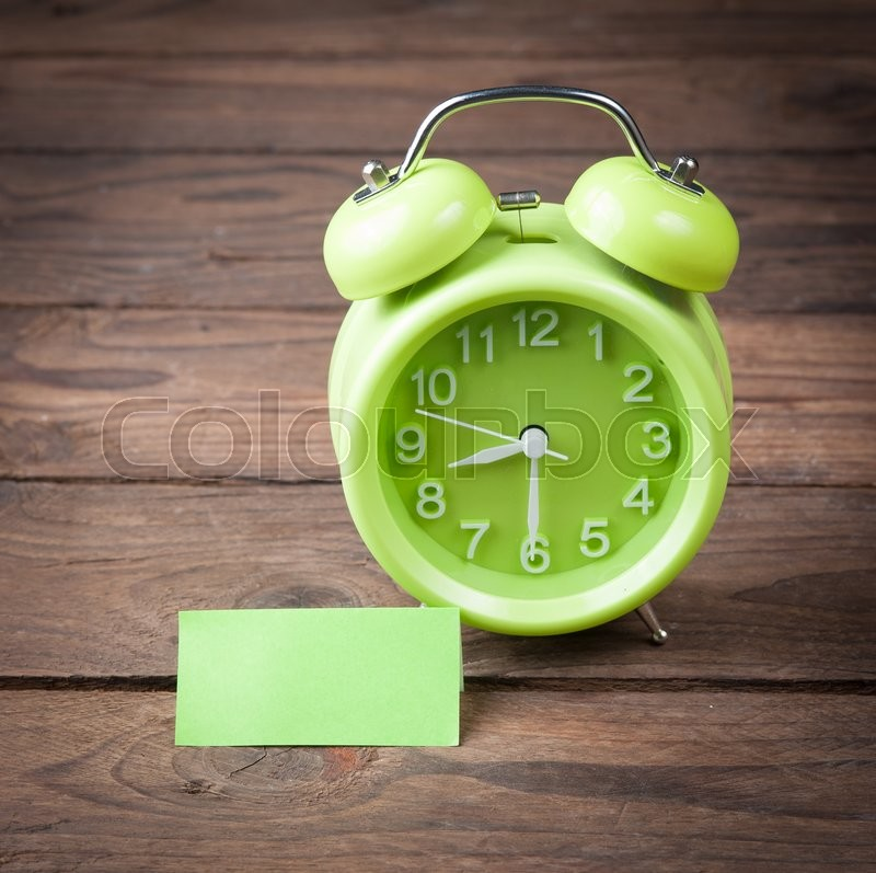 Stock image of 'Green alarm clock and sticky paper with Text Space on wood background'