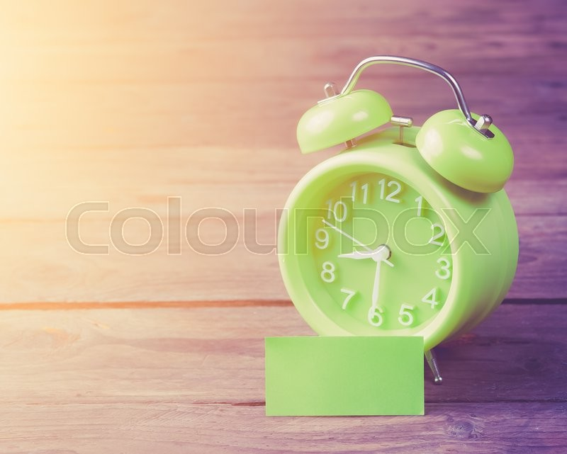 Stock image of 'Green alarm clock and sticky paper with Text Space on wood background,morning light'