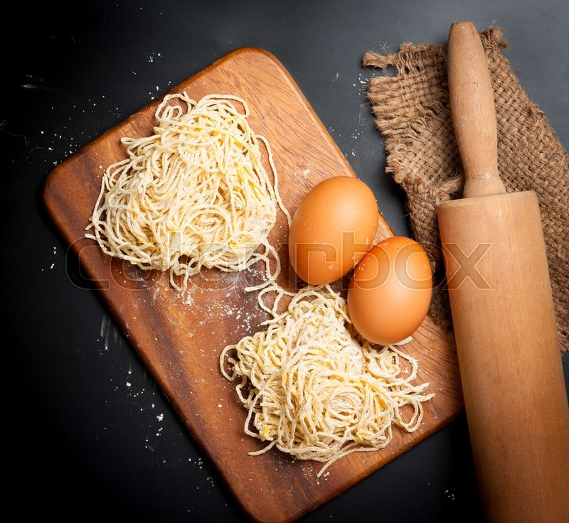 Stock image of 'Yellow noodles drying with eggs on blackboard background'