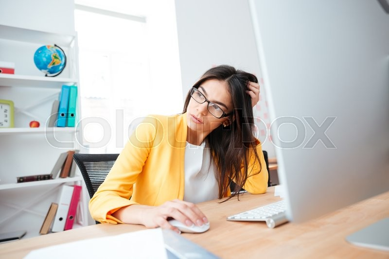 Stock image of 'Pensive businesswoman sitting at the table with computer and looking away in office'