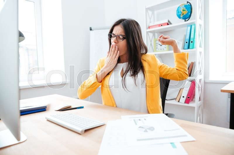 Stock image of 'Young businesswoman yawning in office'