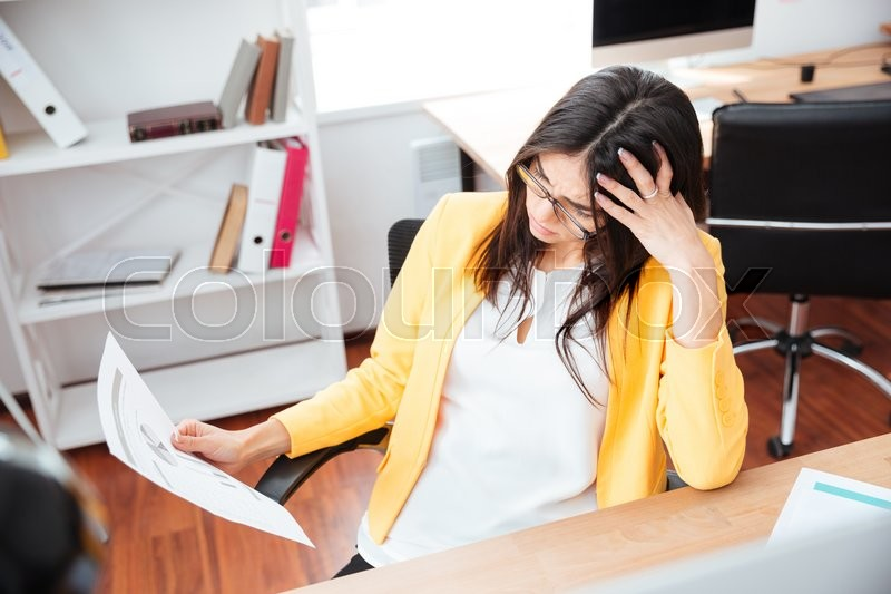Stock image of 'Businesswoman analysing graphics on paper in office'