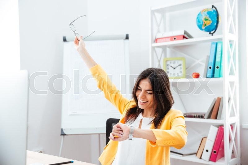 Stock image of 'Smiling successful businesswoman looking on wrist watch in office'
