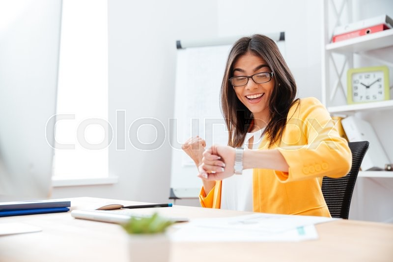 Stock image of 'Happy successful businesswoman looking on wrist watch in office'