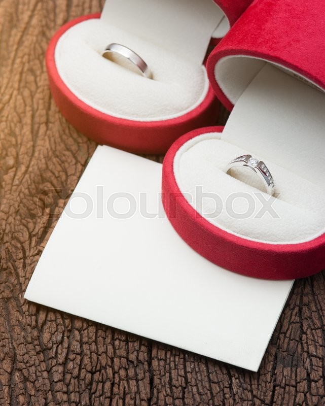 Stock image of 'Diamond ring in red velvet box with blank notepaper on wood'