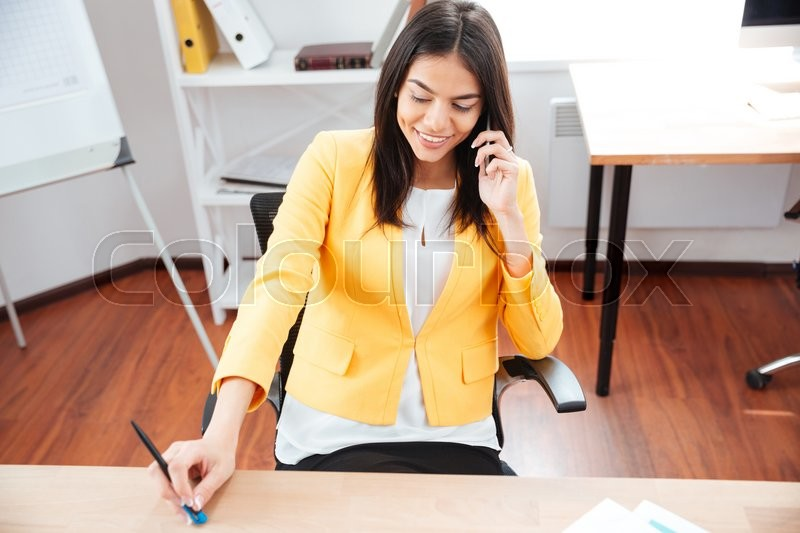Stock image of 'Smiling businesswoman talking on the phone in office'