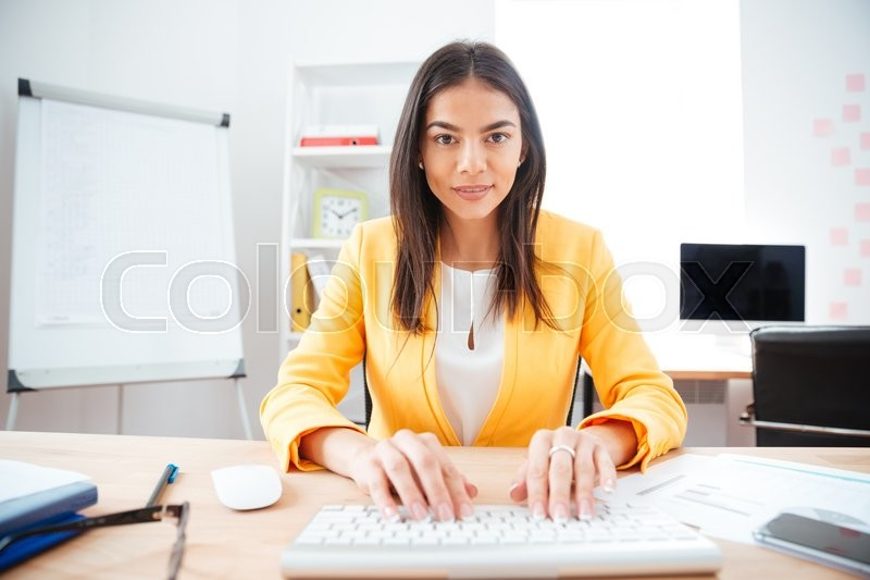 Stock image of 'Happy charming businesswoman typing on keyboard in office'
