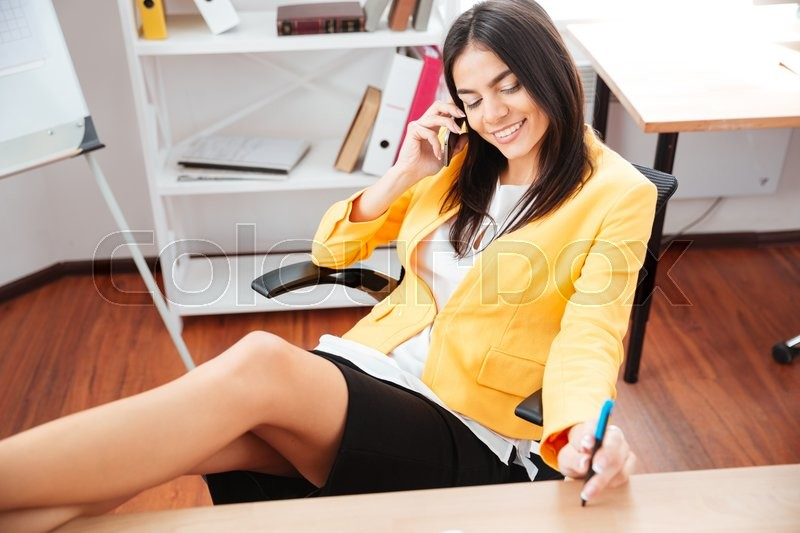Stock image of 'Happy attractive businesswoman talking on the phone in office'