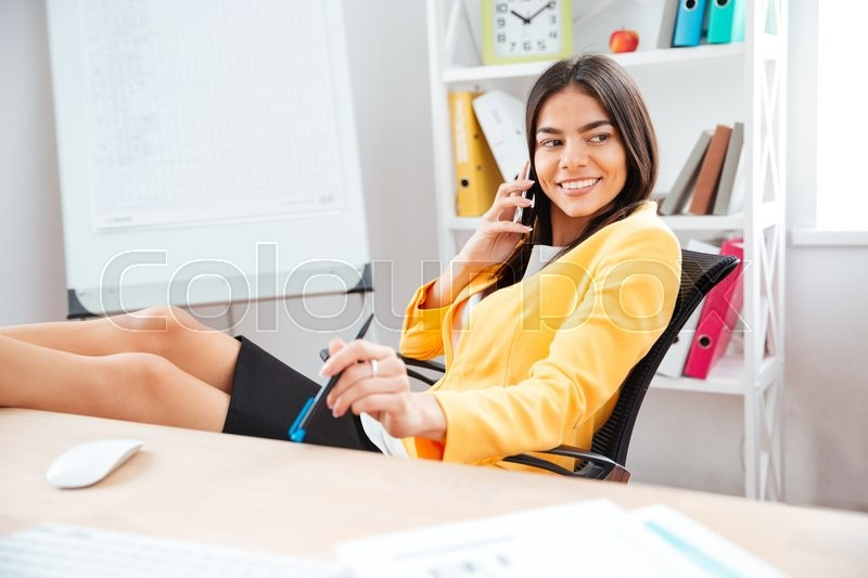 Stock image of 'Smiling businesswoman talking on the phone at her workplace and looking away'
