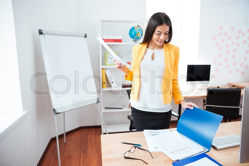 Stock image of 'Happy businesswoman working with papers in office'